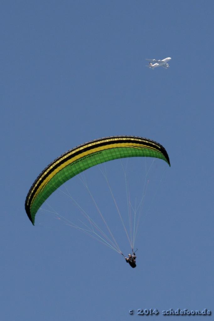 Ein Passagierflugzeug fliegt über einem Gleitschirmflieger