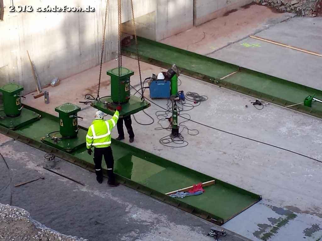 Bauarbeiter platzieren Pressen auf flachen Stahlschienen beim Fundament
