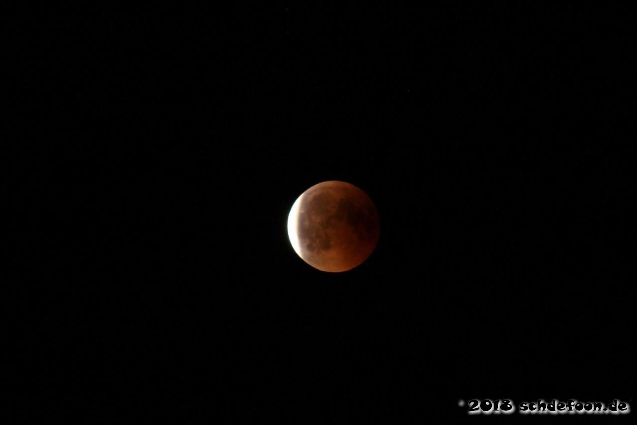 Linke Seite des Mondes leuchtet hell, der restliche Mond ist hellrot