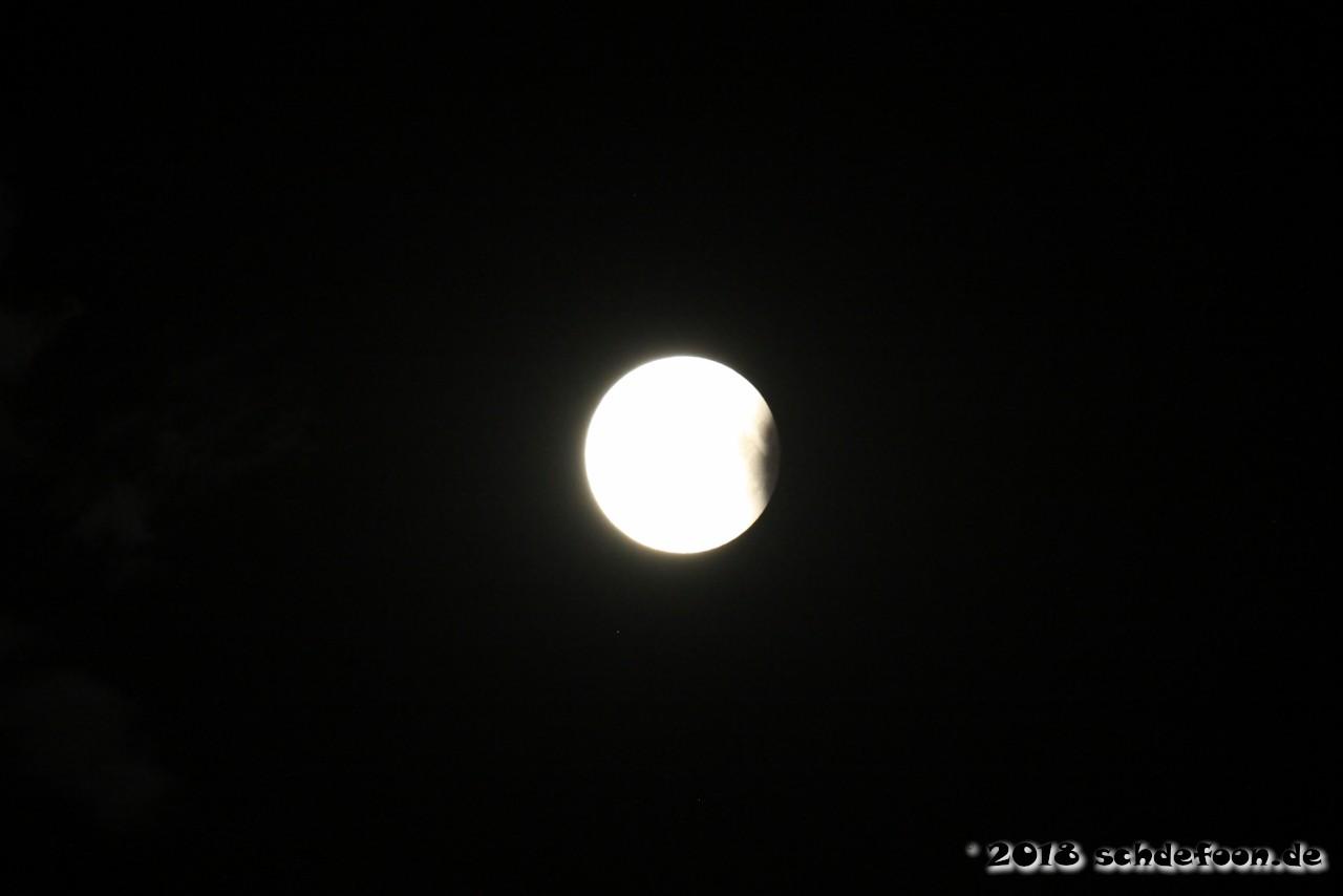 Der Vollmond wird an der rechten Seite von einem Schatten bedeckt