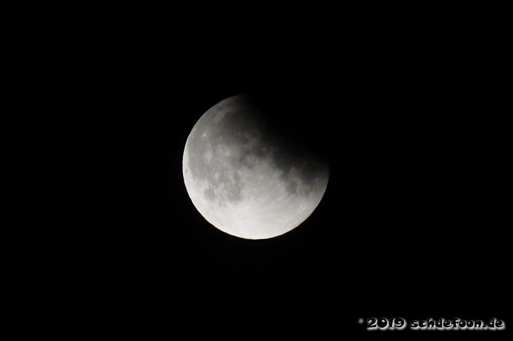 Der Mond ist vom Erdschatten noch etwas verdunkelt