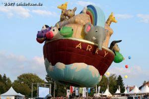 Ein Ballon mit der Form der Arche. Auf der Arche sind Kühe, Krokodile, Giraffen, ein Elefant, ein Affe und andere Tiere zu erkennen