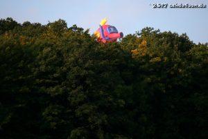 Beim Ballon mit der Form eines Seepferdchens schaut der Kopf über die Wipfel eines Waldes