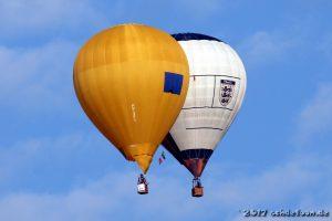 Ein gelber und ein weißer Ballon schweben direkt nebeneinander in der Luft
