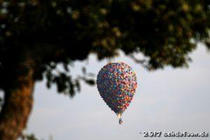 Ein buter Ballon schwebt unter dem belaubten Ast eines Baumes