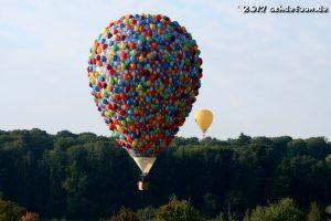 Ein bunter Ballon, der aus tausenden Luftballons zu bestehen scheint schwebt vor dem Wald. Im Hintergrund ist ein gelber Ballon zu sehen