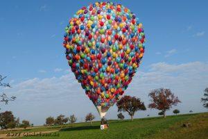 Der bunte Ballon hat auf dem Boden aufgesetzt. Im Hintergrund sind Bäume und blauer Himmel zu sehen