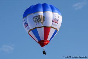 Ein Mann sitzt auf einer Sitzschale, die unten an einem Ballon befestigt ist, der am Himmel schwebt