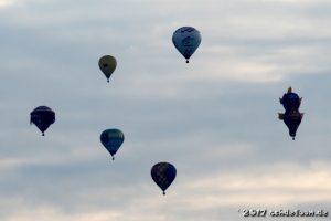 Sechs Ballone schweben am Himmel. Dabei sind auch ein Clowngesicht und ein Seepferdchen