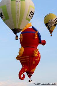 Drei Ballone schweben nebeneinander. Einer davon hat die Form eines Seepferdchens