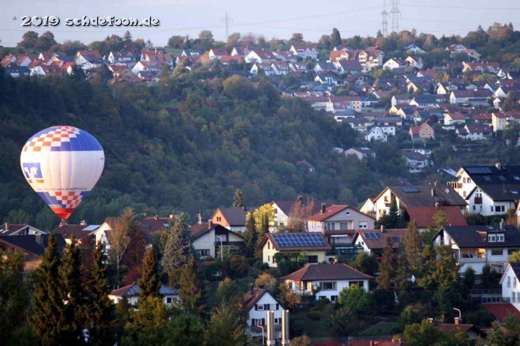 Ein Ballon schwebt durch ein Tal zwischen zwei Dörfern