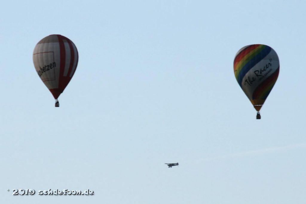 Ein Sportflugzeug fliegt an zwei Ballonen vorbei