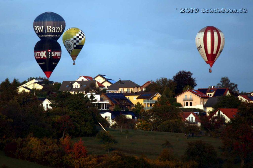 Vier Ballone schwegen dicht über Häusern eines Dorfes