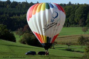 Ein bunter Ballon steht auf einer Wiese neben seinem Transportfahrzeug