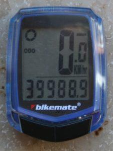 Ein Fahrradtacho mit blauem Rahmen zeigt 39988 Kilometer an
