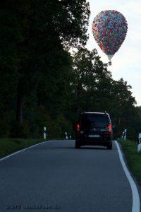 Ein bunter Heißluftballon schwebt über einer Landstraße, auf der ein schwarzes Auto fährt