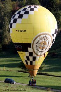 Ein gelber Heißluftballon mit der Aufschrift Warsteiner steht neben einem Servicefahrzeug auf einer Wiese
